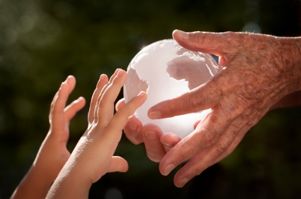 Close up of a crystal globe passing from an old woman's hand to the little child's outstretched hands in front of a dark foliage defocused background. Small amount of digital noise added.