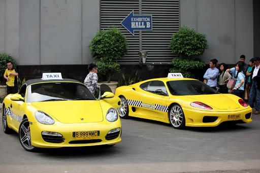 Beberapa orang menunggu antrian naik taksi Porsche Boxster S dan Ferrari Modena 360 pada saat acara uji coba untuk masyarakat di Kawasan Gelora Bung Karno - Senayan, Jakarta, Sabtu (14/07). Perusahaan  MMCab meluncurkan Taksi Porsche Boxster S dan Ferrari Modena 360 dengan mengutamakan prinsip smart, simple, dan efficient. Dalam rangka promosi, taksi mewah tersebut tidak dikenakan biaya sampai dengan tanggal 18 Juli 2012.---JP/NURHAYATI---