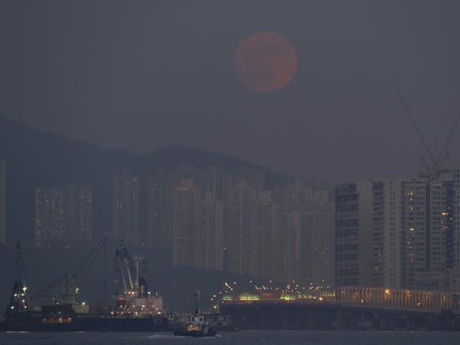 Mặt trăng mọc trên Victoria Habour tại Hồng Kông. Hình: AP Photo / Vincent Yu.